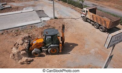 Road construction work. Mini loader removes stones and...