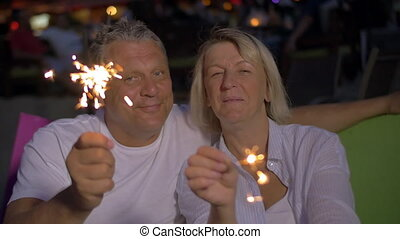 Senior couple with Bengal lights outdoor at night - Slow...