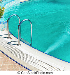 Swimming pool with stair and blue relaxing water in a hotel