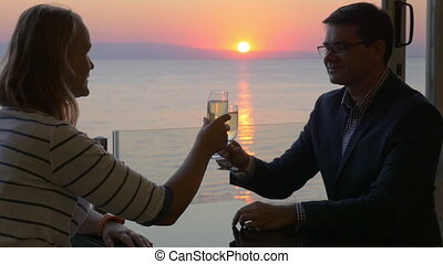 Couple toasting with wine and enjoying sunset over sea -...