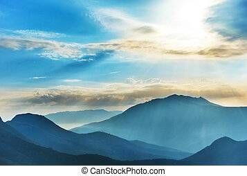 Blue high mountains and sunset shining sun