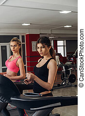 Two girls on a treadmill