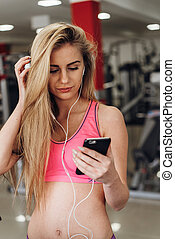 Blonde with a phone  at the gym. Listening to music