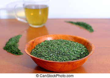 Dried nettle in a wooden bowl with a cup of nettle tea
