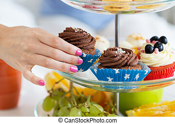 close up of hand taking cupcake from cake stand - people,...