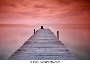 Lonely person sitting on pier - Unrecognizable person...