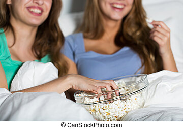 happy women eating popcorn and watching tv at home -...