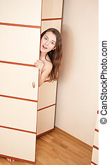 Surprised girl is hiding in wardrobe - Surprised young girl...