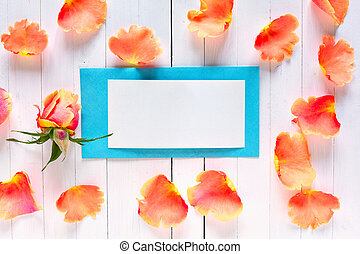 Light blue envelope with a place for signatures among rose petals