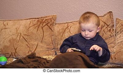 little boy plays game on a smartphone.