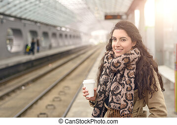 Smiling woman in coat with coffee at station - Single...