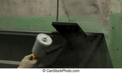 Man painting steel locker, industrial shooting