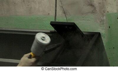 Man painting steel locker, industrial shooting