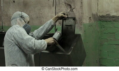 Man painting iron locker, industrial shooting