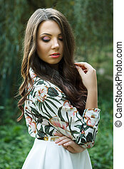 Beautiful brunette woman poses outdoors - Portrait of...