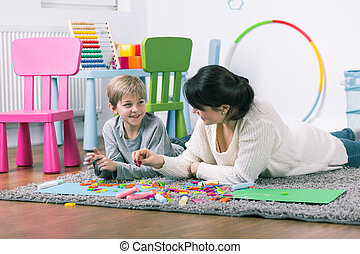 Having fun together - Young psychologist and little boy...