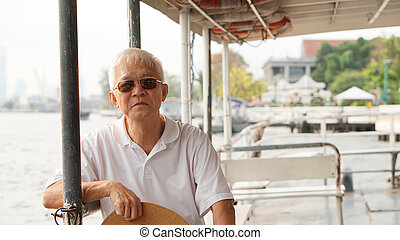 Senior Asian man riding a ferry boat to cross Chaopraya...