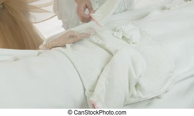 Masseuse put off white mitten from woman hand in beauty...