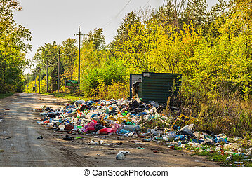 Garbage in landfill near forest