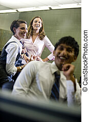 Three college students hanging out in classroom