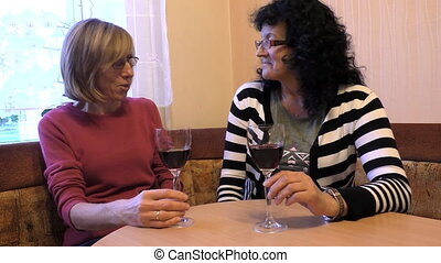 Two ladies drinking wine - Two middle age women friends...
