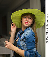 Flirty woman in green hat and blue jeans jacket