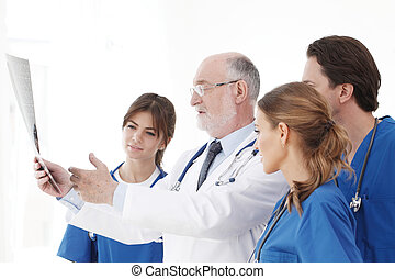 Medical team checking X-ray results - Medical team checking...