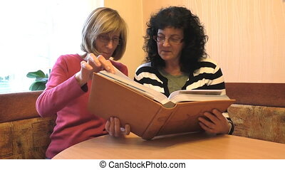 Two ladies watching album - Two middle aged female friends...