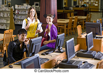 Three college students hanging out in library - Two pretty...