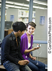 Two college students with music players in library - Two...