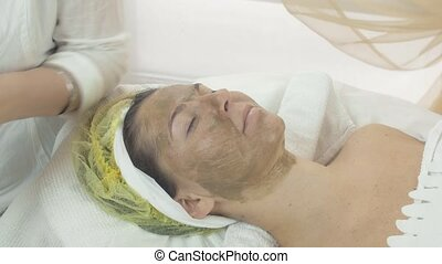 Girl face with green clay cosmetic mask in beauty saloon...