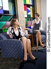 Pretty young women sitting on waiting room chair -...