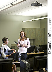 Two young women conversing in computer lab - Two young...