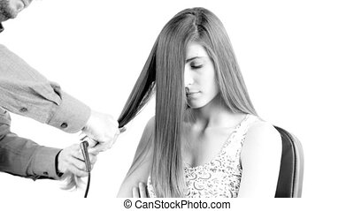 Beautiful woman getting long hair straightened with comb and iron by hairdresser dolly shot isolated 4K black and white