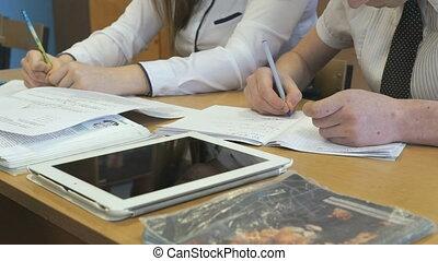 Two schoolgirls sit at desk in school