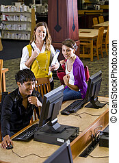 College students using computer in library - Male college...