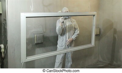 Man painting window with powder - Worker in white protect...