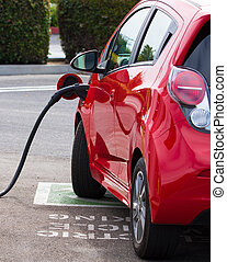 Electric Car Charging - An electric vehicle, car charging at...