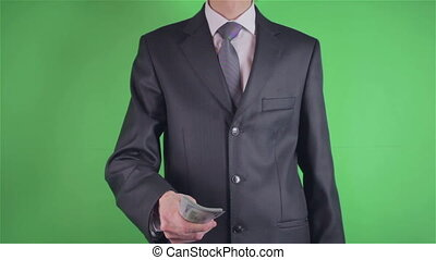 Handsome young man offer money on chroma key or Green screen