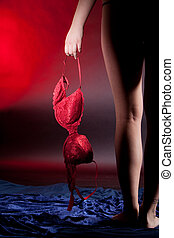 woman holding a red bra - Silhouette of woman legs and hand...