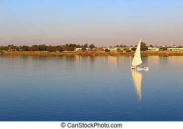 Felluca with white sails, sailing along the Nile River in...