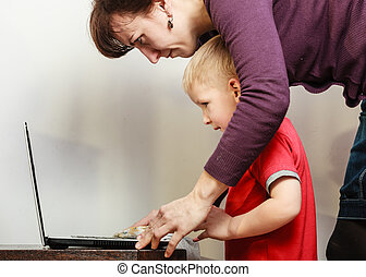 Little boy with laptop and mother helping - Technology and...