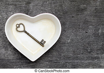 vintage key and heart shape plate on grunge wooden...