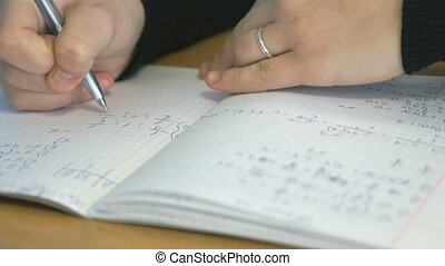 Student writes text in a notebook Closeup - Student writes...