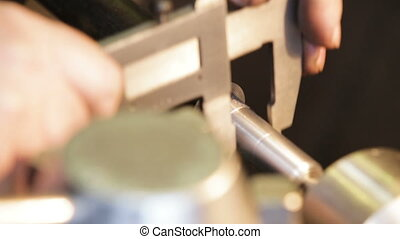 Operator measuring dimensions with calipers on milling...