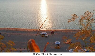 Sunset beach with recreational boats and sun flares on sea surface