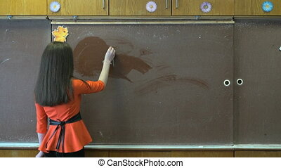 Girl writes words on school board using a chalk - Young girl...
