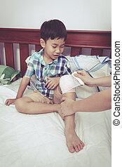 Child injured Mother bandaging sons knee Vintage style -...
