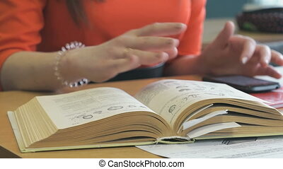 Schoolgirl sits at a desk, leafing through a book -...