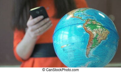 Young girl stands in front of a world globe - Young girl in...